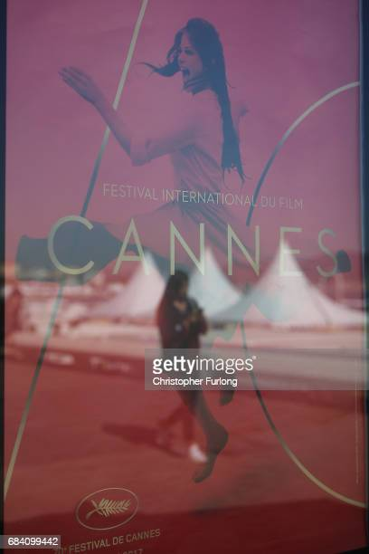 A woman walks along The Croisette and is reflected in a festival poster on the first day of the 70th annual Cannes Film Festival at the Palais des...