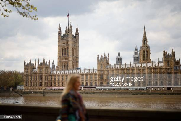 Woman walks along the embankment opposite the Houses of Parliament in central London on April 30, 2021.