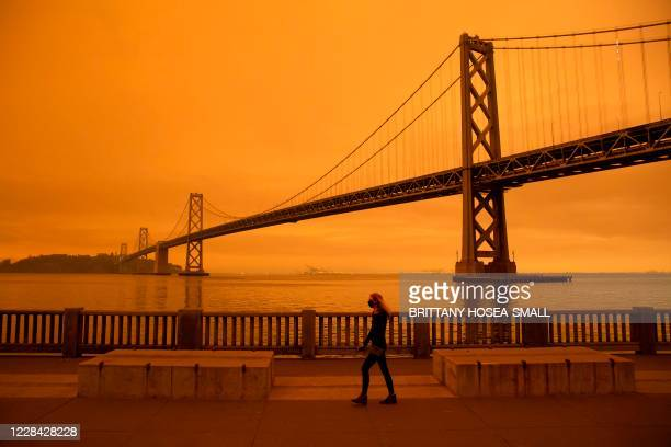 Woman walks along The Embarcadero under an orange smoke-filled sky in San Francisco, California on September 9, 2020. - More than 300,000 acres are...