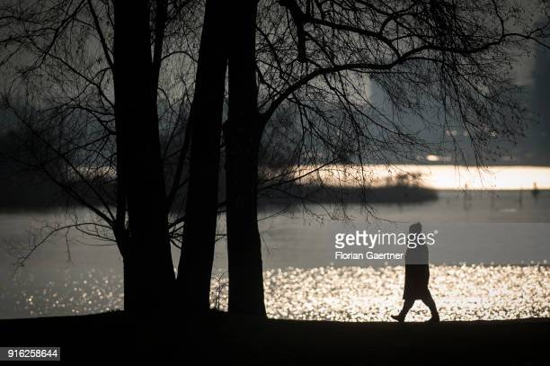 A woman walks along the Havel river during sunset on February 09 2018 in Berlin Germany