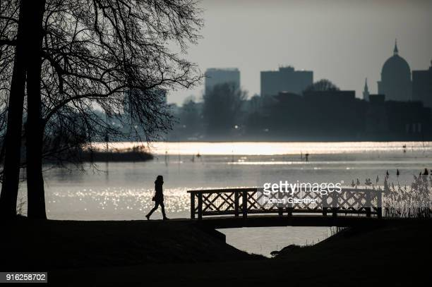 A woman walks along the Havel river in front of the cityscape of Potsdam during sunset on February 09 2018 in Berlin Germany