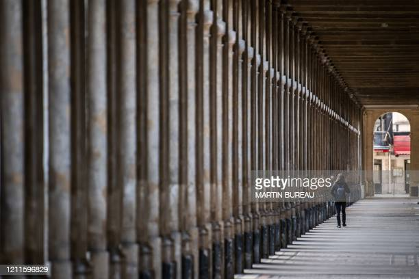 A woman walks along the Jardin du Palais Royal on May 2 in Paris on the 47th day of a strict lockdown in France aimed at curbing the spread of COVID19