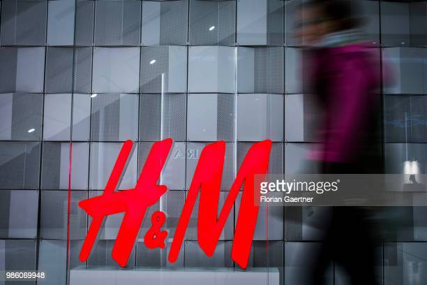 A woman walks along the logo of HM on June 23 2018 in Berlin Germany