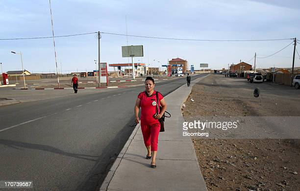 A woman walks along the main street of Tsogttsetsii the South Gobi desert Mongolia on Wednesday June 5 2013 Mongolia a country of almost 29 million...