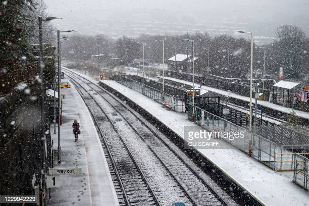 Woman walks along the platform of the railway station as snow falls in the village of Marsden, near Manchester in northern England on December 4,...