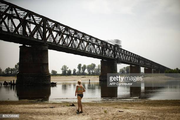 A woman walks along the Po River near the Ponte della Becca bridge in Linarolo near Pavia northern Italy on August 1 as the country is affected by a...