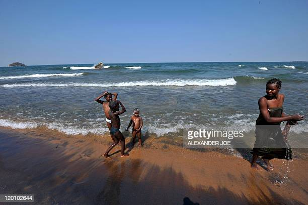 A woman walks along the Saga beach as children wash themselves at Lake Malawi on July 17 2011 Lake Malawi remains unspoilt and one of Malawi's'...