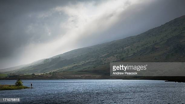 A woman walks along the shore of Llynnau Mymbyr