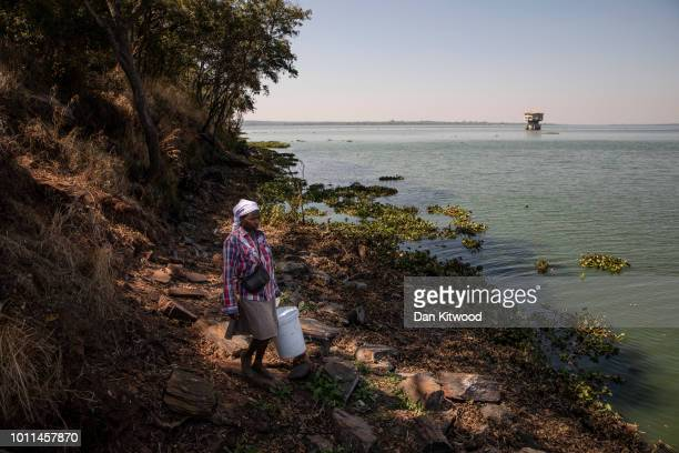 A woman walks along the shore with a bucket of illegally caught fish on Lake Chivero on August 5 2018 in Harare Zimbabwe Lake Chivero is 32km South...
