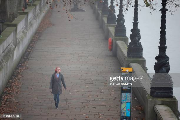 Woman walks along the south bank beside the River Thames in the fog in London on December 8 as talks on a trade deal between the EU and the UK enter...