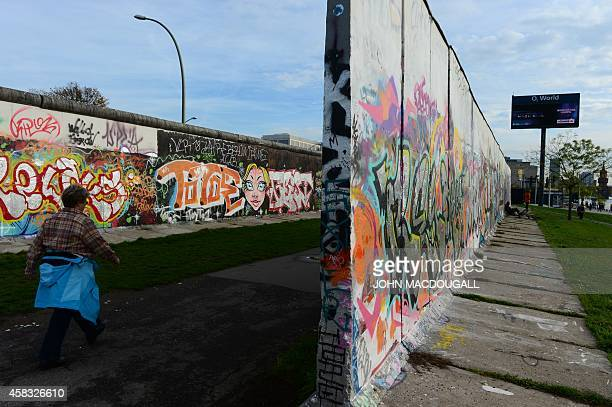 A woman walks along the 'west side' of the East Side Gallery a stretch of the Berlin wall in Berlin on November 3 2014 This stretch of the Berlin...