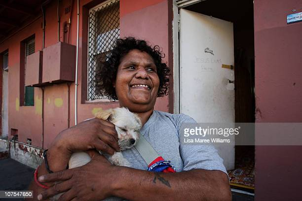 """Woman walks along Vine Street holding her dog in the Aboriginal housing community known as """"The Block"""" in Sydney, Australia. Thirty-seven years since..."""