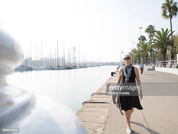Woman walks along waterfront promenade