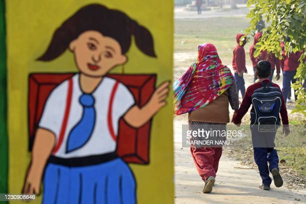 Woman walks along with her child at a government school on the outskirts of Amritsar on February 1, 2021.