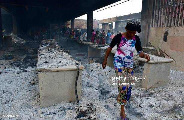 A woman walks amid ashes in the market after a fire devastated the building during the night on September 18 2017 in Abobo neighborhood of Abidjan /...