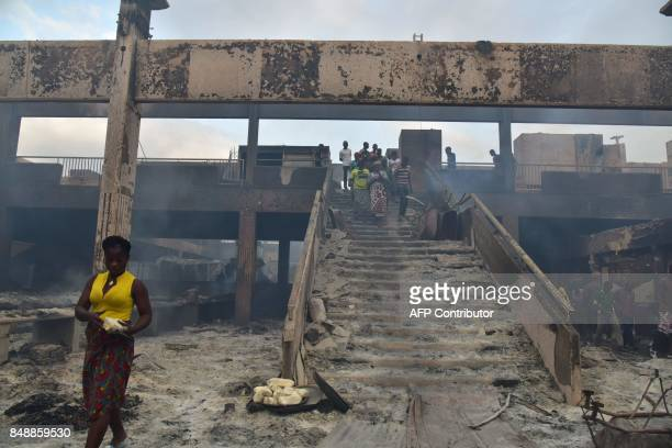 A woman walks amid debris in the market after a fire devastated the building during the night on September 18 2017 in Abobo neighborhood of Abidjan /...