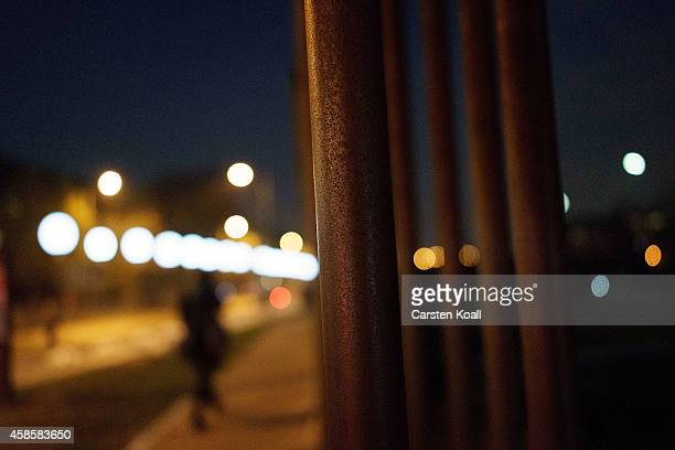 Woman walks among a light installation of balloons tethered to lamps illuminating the course of the Berlin Wall along the Bernauer Strasse two days...