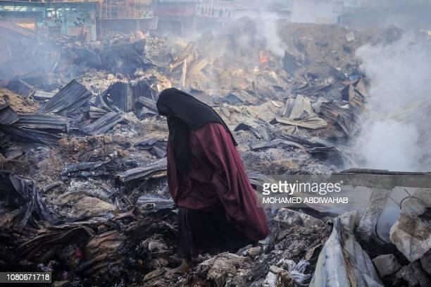TOPSHOT A woman walks among debris after a fire broke overnight in Mogadishu's biggest market the Bakara Market on January 11 2019