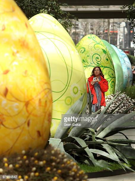 A woman walks among giant Easter eggs coloured in the numerical progression of colours within the colour spectrum at the Arkaden shopping mall on...