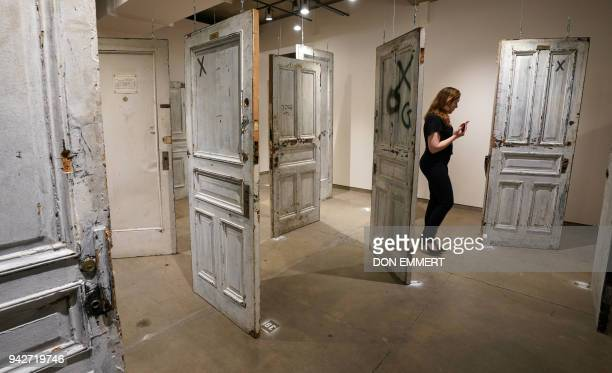 Woman walks amongst the Chelsea doors on display at Ricco/Maresca Gallery April 6, 2018 in New York. - The 'Chelsea Doors' auction, featuring...