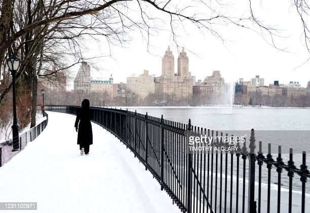 Woman walks around the Jacqueline Kennedy Onassis Reservoir in Central Park in the borough of Manhattan, New York City, February 1, 2021.