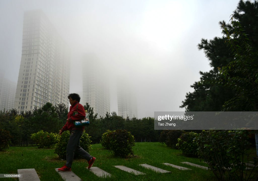 A woman walks at the Changjiang street during dense fog enveloping Harbin on September 14, 2018 in Harbin, China. The meteorological department issued a yellow alert for dense fog
