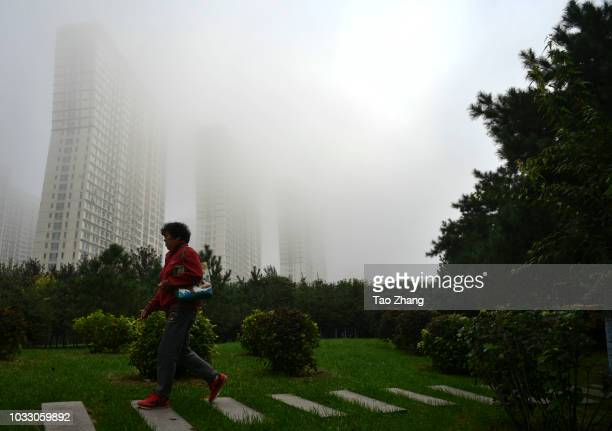 A woman walks at the Changjiang street during dense fog enveloping Harbin on September 14 2018 in Harbin China The meteorological department issued a...