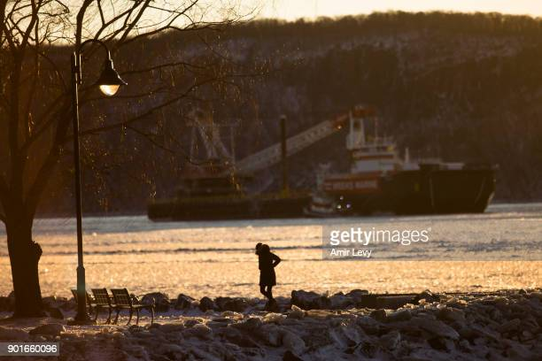 A woman walks at the Hudson River waterfront on January 5 2018 in Dobbs Ferry New YorkExtreme low tempratures and wind are expected throghout the...