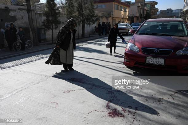 Woman walks at the site where gunmen shot dead two Afghan women judges working for the Supreme Court, in Kabul on January 17, 2021. - Gunmen shot...