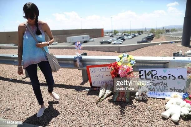 A woman walks away from a makeshift memorial outside Walmart near the scene of a mass shooting which left at least 20 people dead on August 4 2019 in...