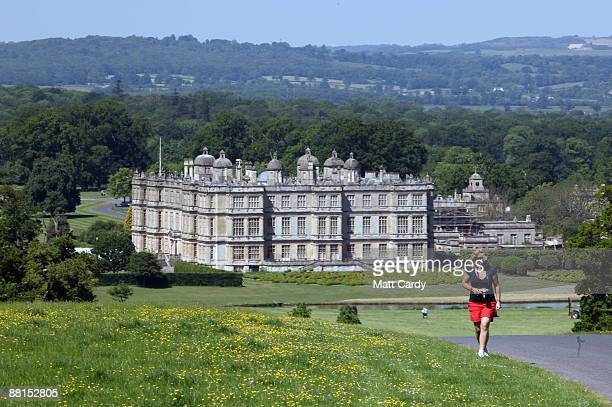 A woman walks away from Longleat house as professional window cleaners Nick Walker and Daniel Barr clean the windows at the front of Longleat House...