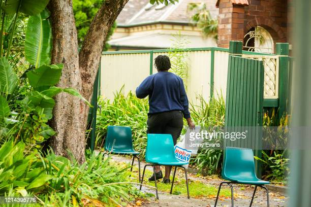 A woman walks away with bags of food at St Paul's Anglican Church in Burwood on March 24 2020 in Sydney Australia The Parish Pantry provides food for...