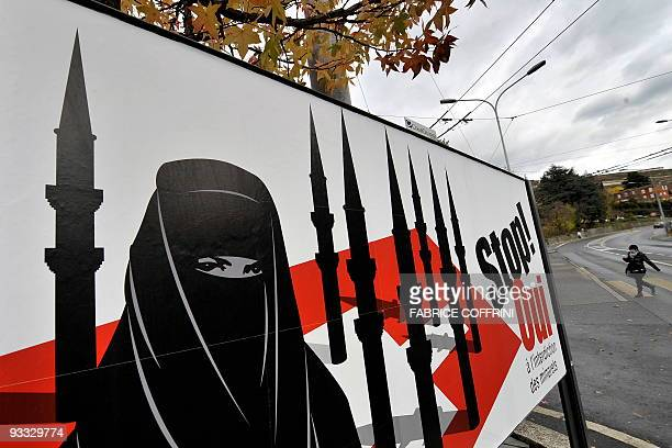 A woman walks behind a campaign posters of the farright Swiss People's Party depicting a woman wearing a burqa against a background of a Swiss flag...