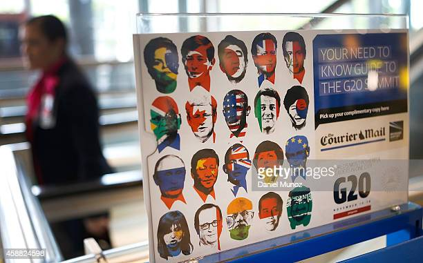 A woman walks behind advertisment of the local newspaper with the G20 leaders faces painted in their own country flag colors at Brisbane airport on...