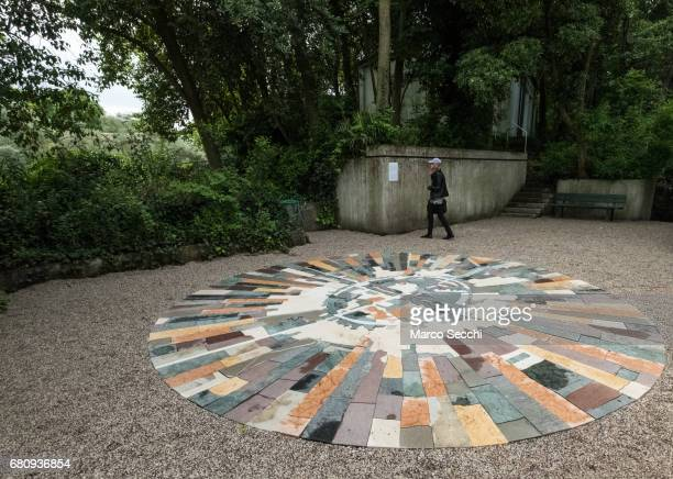 """Woman walks behind the installation by Gal Weinstein """"Marble Sun"""" at the Israeli pavilion on May 9, 2017 in Venice, Italy. The 57th International Art..."""
