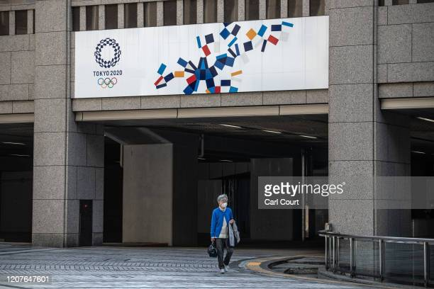 Woman walks beneath a Tokyo 2020 Olympics banner on March 19, 2020 in Tokyo, Japan. As Japanese and IOC officials continued to insist that the Games...