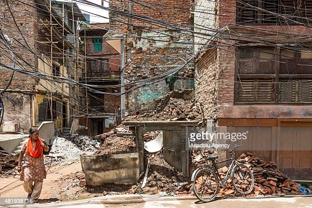 Woman walks beside a destroyed building in Kathmandu, Nepal on July 25, 2015.. Today marks the 3 month anniversary of the Nepal earthquakes which at...