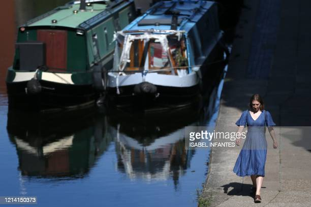 Woman walks beside Regent's Canal in London on May 20 as temperatures in the capital are expected to reach 28C . - Britain's official coronavirus...