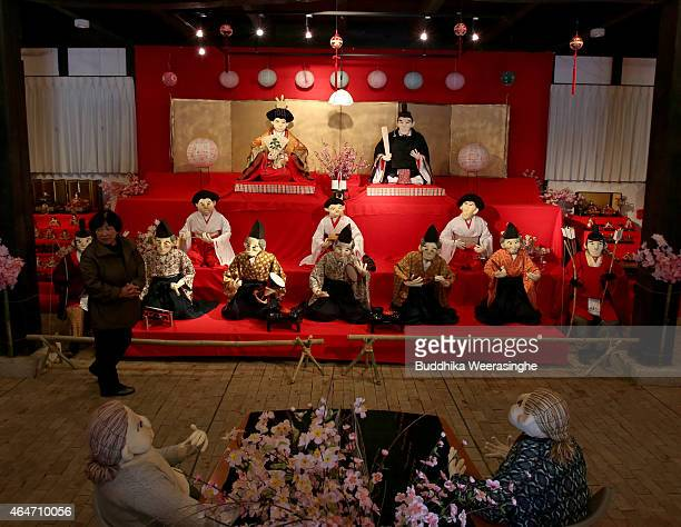 A woman walks beside the illustration showing human size scarecrows as hina doll dressed in traditional Japanese Hinamatsuri costumes are on display...