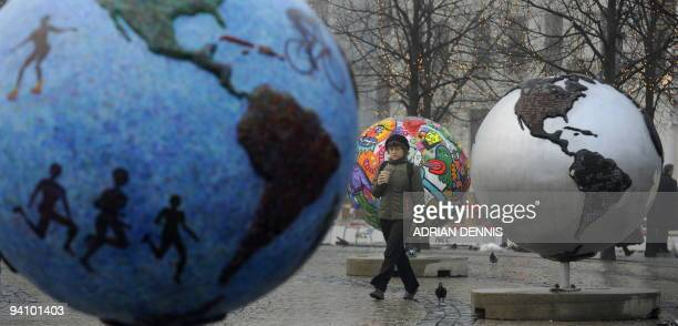 A woman walks between a display entitled 'Cool Globes' an exhibition about combating global warming and climate change in the Kongens Nytorv area in...