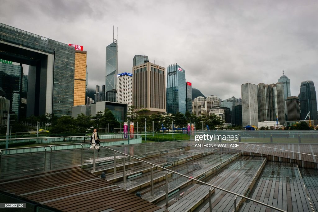 A woman walks between exhibits at the Harbour Arts Sculpture Park in Hong Kong on February 22, 2018. Hong Kong's harbourfront is known for glistening skyscrapers and the sight of containerships navigating busy shipping lanes -- but a new art project has added a giant pumpkin, a map of the stars and a pair of disembodied legs to the famous skyline. /