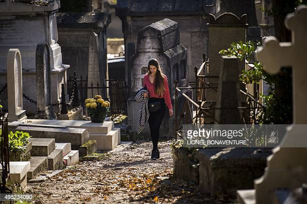 A woman walks between graves in the Pere Lachaise cemetery on November 1 2015 in Paris during the AllSaints Day AFP PHOTO / LIONEL BONAVENTURE / AFP...