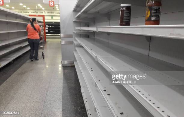 A woman walks between the empty shelves of a supermarket in Caracas on January 11 2018 Colombian President Juan Manuel Santos on Thursday called his...