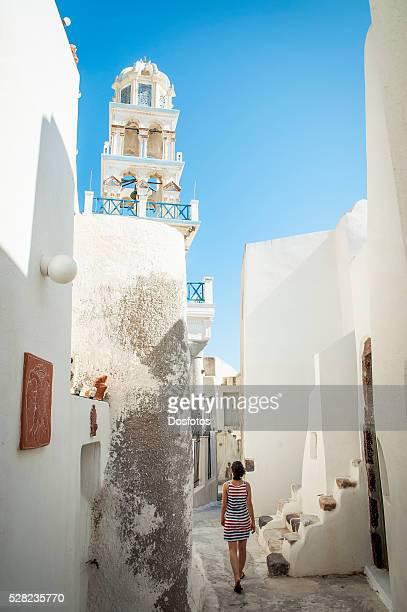 A woman walks between whitewash buildings; Megalochori, Santorini, Greece