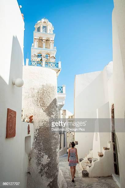 A woman walks between whitewash buildings