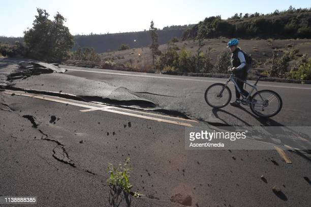 woman walks bicycle along broken road - earthquake stock pictures, royalty-free photos & images