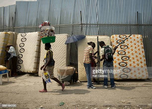 A woman walks buy mattresses for sale with a tub on her head full of sundires she is selling on the steets of PortAuPrince Haiti March 31 2011 |...