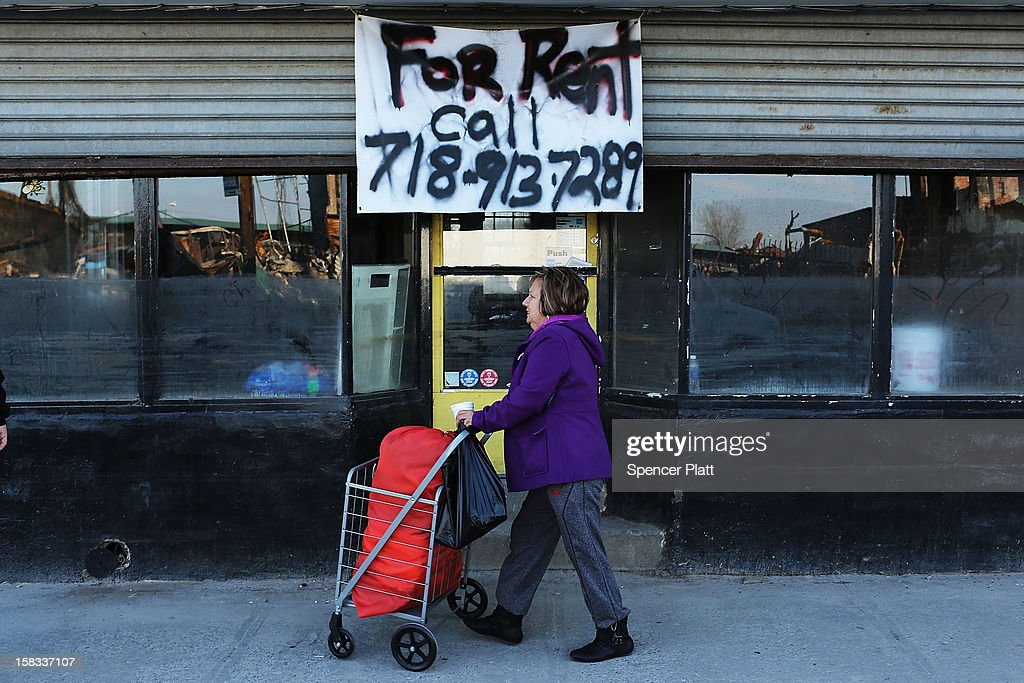 A woman walks by a closed business near the beach in Rockaway on December 13, 2012 in New York City. Much of the Rockaway neighborhood is still suffering the effects of Hurricane Sandy which caused extensive damage to parts of New York, New Jersey and Connecticut. Thousands of Rockaway residents and business owners are still unable to return to their properties while electricity remains sporadic in many neighborhoods.