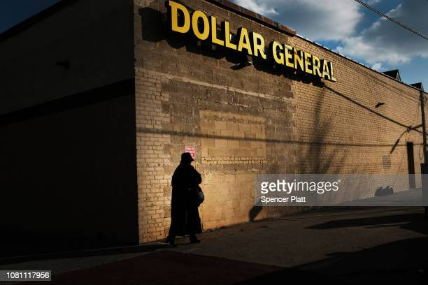 A woman walks by a Dollar General store on December 11 2018 in the Brooklyn borough of New York City As the income gap between rich and poor...