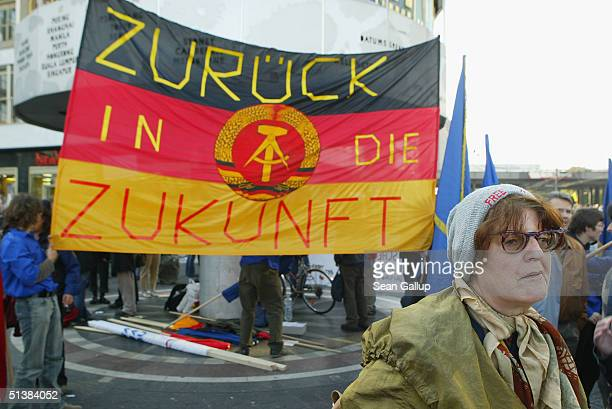 A woman walks by a flag of the former East Germany that reads Back to the Future during a protest against proposed German economic reforms known as...